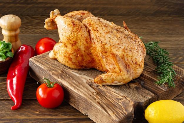 Pollo arrosto con spezie su fondo di legno. cibo sano, dieta o concetto di cucina.