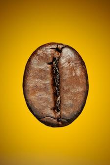 Chicco di caffè tostato su uno sfondo giallo