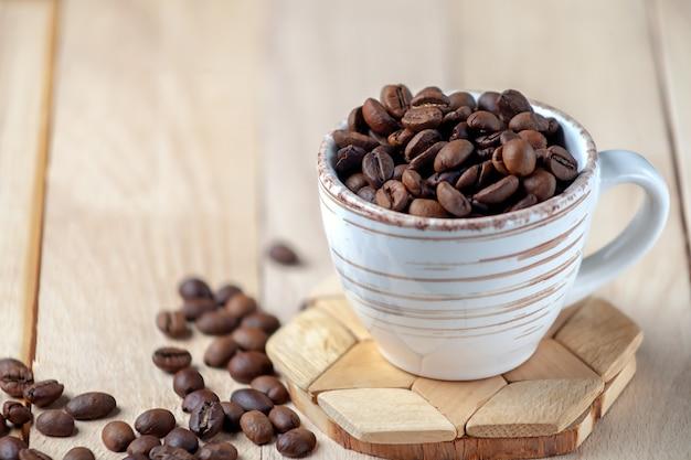Chicchi di caffè tostati in uno spazio di copia simbolica dell'immagine di una tazza di ceramica