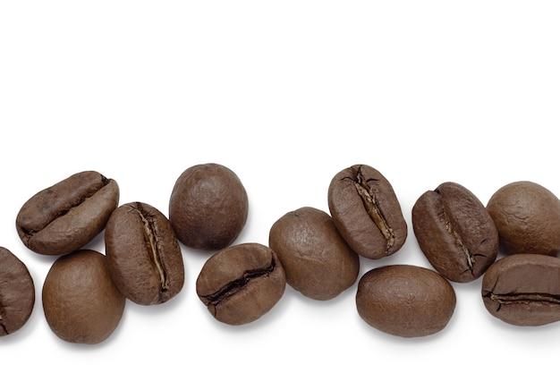 Chicchi di caffè tostati da vicino isolati su sfondo bianco