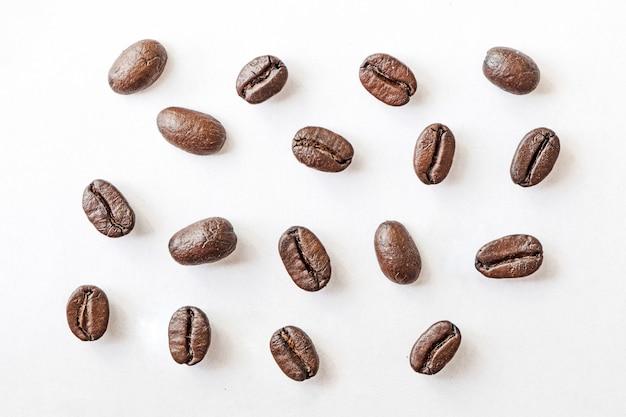 Close-up di chicchi di caffè arrostiti su uno sfondo bianco. foto a macroistruzione chicchi di caffè. isolato su sfondo bianco