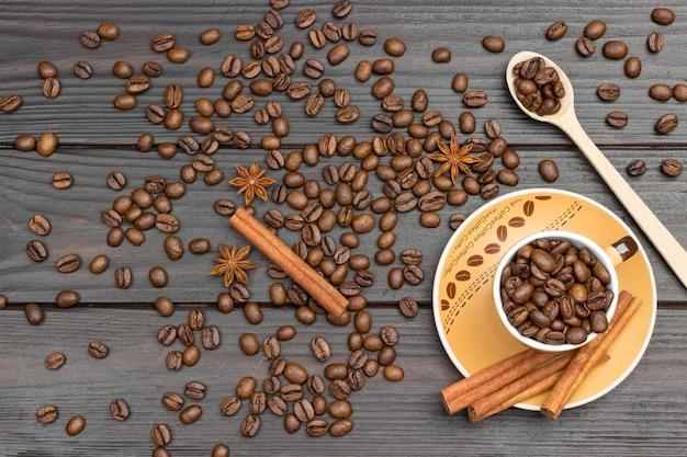 Chicchi di caffè tostati in tazza e cucchiaio di legno. bastoncini di cannella sul piattino. chicchi di caffè e anice stellato sul tavolo. fondo di legno scuro. lay piatto