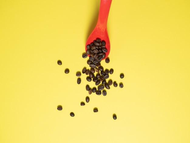 Chicchi di caffè tostati che cadono dal mestolo di metallo isolato su bianco