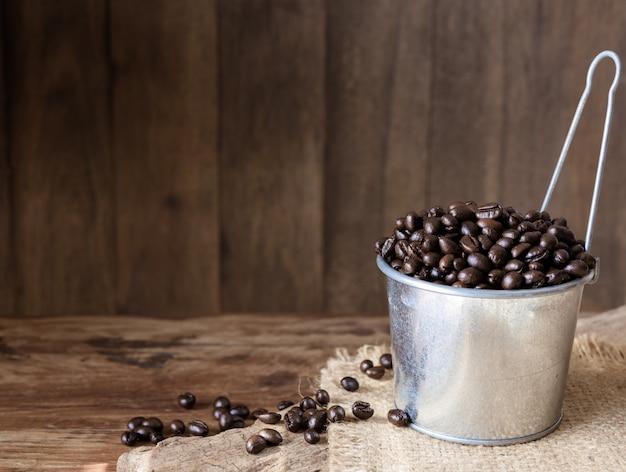Chicchi di caffè arrostiti in latta galvanizzata sopra il fondo di legno di lerciume