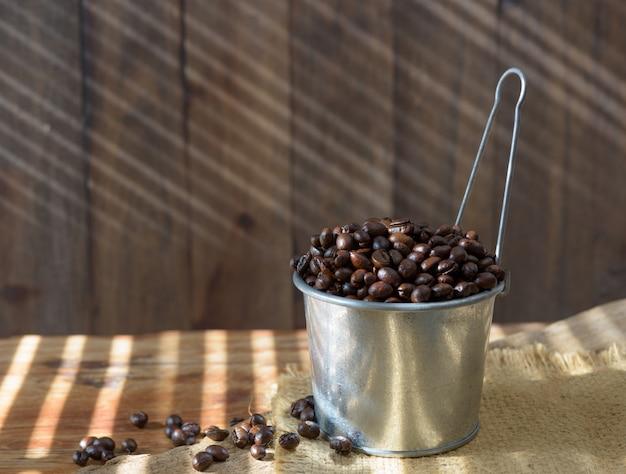 Chicchi di caffè arrostiti in latta galvanizzata sopra la tavola di legno di lerciume