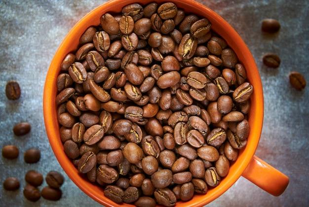 Chicchi di caffè tostati in una tazza arancione su sfondo argento