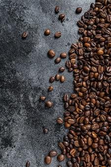 Chicchi di caffè tostati sulla tavola rustica sulla tavola nera. vista dall'alto.