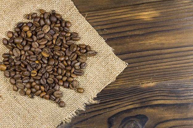 Chicchi di caffè tostati su tela di sacco su tavola di legno