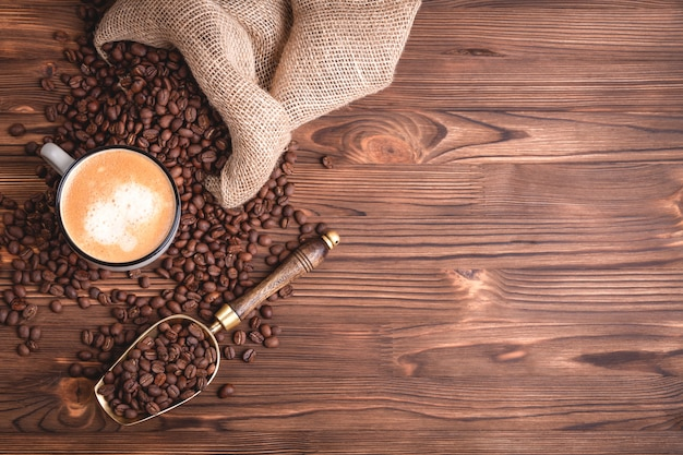 Chicchi di caffè arrostiti che svegliano da una borsa del caffè della iuta su una vecchia tavola di legno.