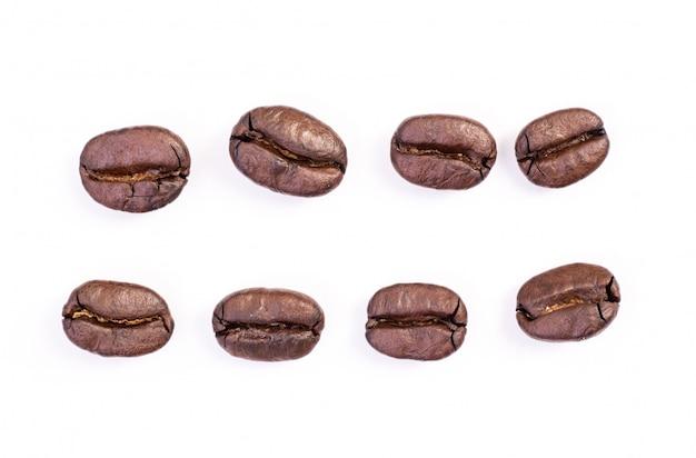 Chicchi di caffè tostati su bianco