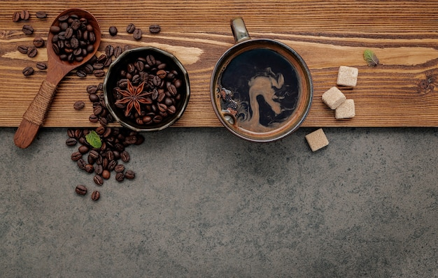 Chicchi di caffè tostati con impostazione della tazza di caffè su sfondo di pietra scura.