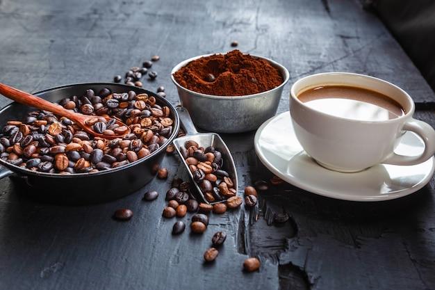 Chicchi di caffè tostati con polvere di caffè e tazze di caffè.