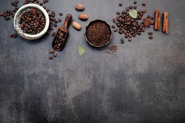 Chicchi di caffè tostati con polvere di caffè e ingredienti saporiti per preparare gustosi caffè su pietra scura.