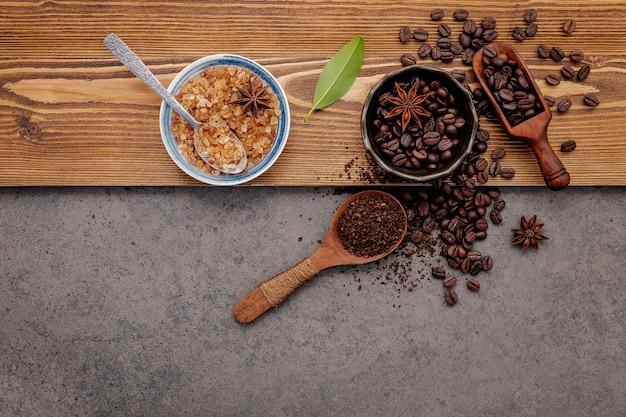 Chicchi di caffè tostati con installazione in polvere di caffè su pietra scura.