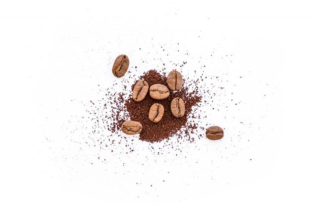 Chicchi di caffè arrostiti con caffè macinato su fondo bianco