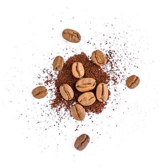 Chicchi di caffè tostati con caffè macinato su sfondo bianco