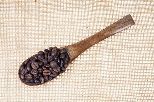 Chicchi di caffè tostati in un cucchiaio di legno.