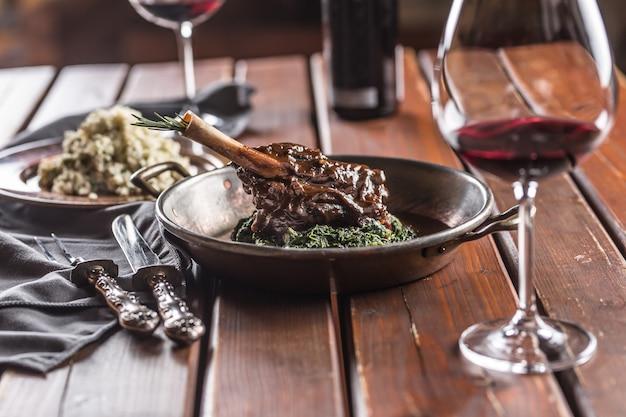 Cosciotto di agnello arrosto o confit in padella con spinaci e vino rosso.