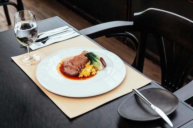 Petto d'anatra arrosto con crema di mais e pollame di tamarindo, servito con pane e burro.