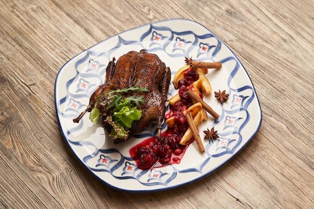 Anatra arrosto con mele cotogne sul fondo della tavola in legno. anatra intera al forno con salsa di mele cotogne e frutti di bosco.