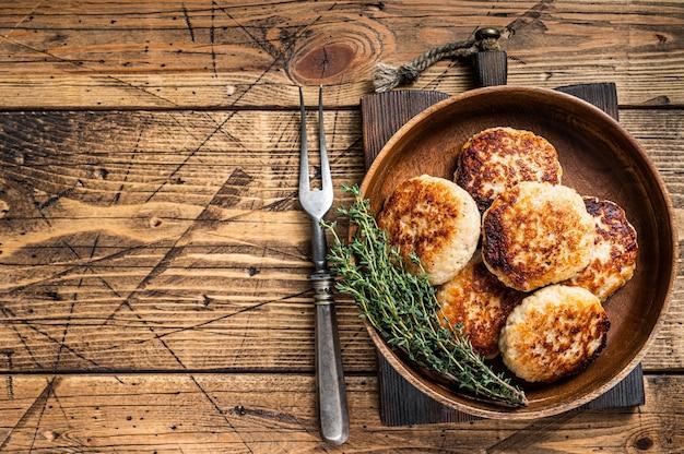 Cotolette di pesce arrosto o tortino in un piatto di legno. fondo in legno. vista dall'alto. copia spazio.