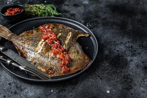 Pesce piatto o passera di mare arrosto in salsa di pomodoro. vista dall'alto.