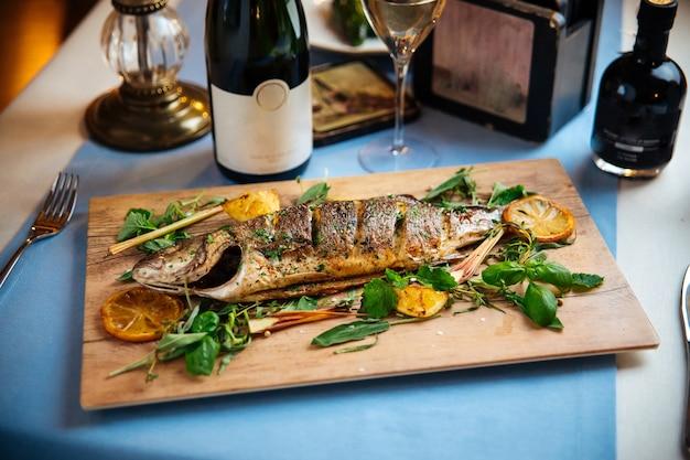 Pesce gourmet arrosto sulla tavola di legno con vino