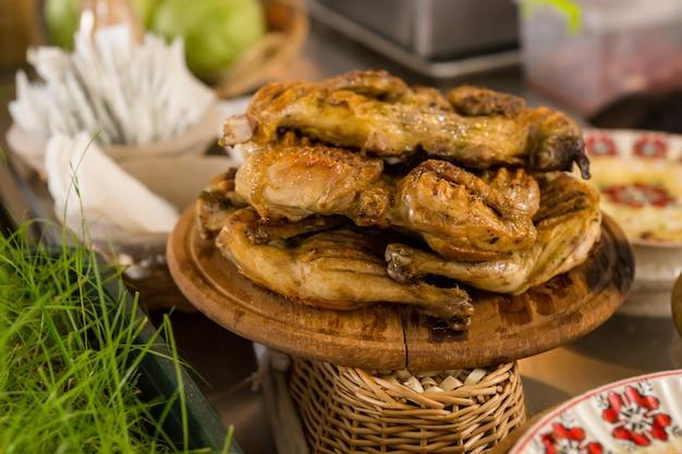 Cosce di pollo alla griglia arrosto impilate su un piatto di legno e servite sul tavolo circondate da altri piatti