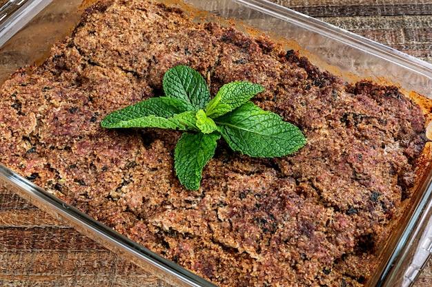 Kibe arrosto nella ciotola di vetro con menta, aglio e cipolla. spuntino brasiliano (kibe de forno). messa a fuoco selettiva.
