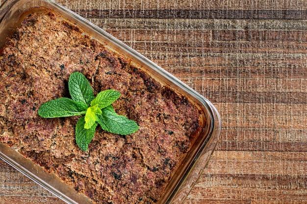 Kibe arrosto nella ciotola di vetro con menta, aglio e cipolla. spuntino brasiliano (kibe de forno). spazio per il testo. vista dall'alto.