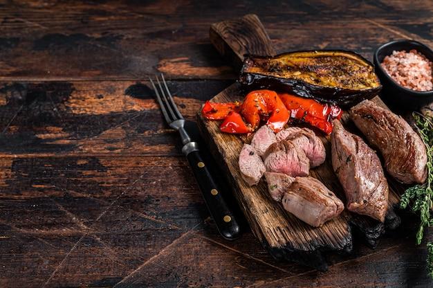 Bistecca di filetto di filetto di agnello arrosto sul tagliere di legno. tavolo in legno scuro. vista dall'alto.