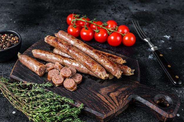 Salsiccia di carne arrosto su una tavola di legno con erbe e pomodoro. sfondo nero. vista dall'alto.