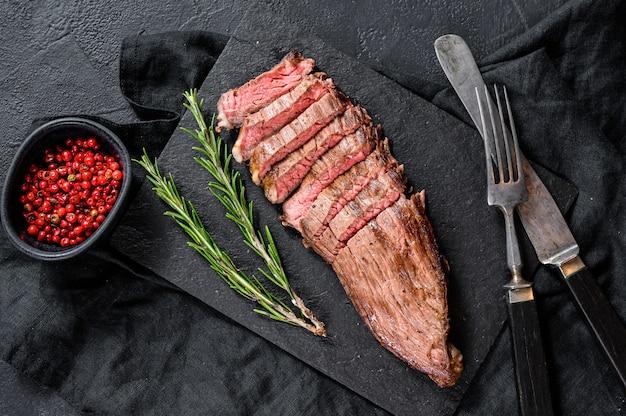 Bistecca di manzo affettata rara mediamente arrostita. sfondo nero. vista dall'alto Foto Premium