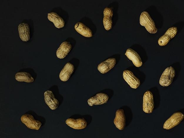 Arachidi tostate su sfondo nero