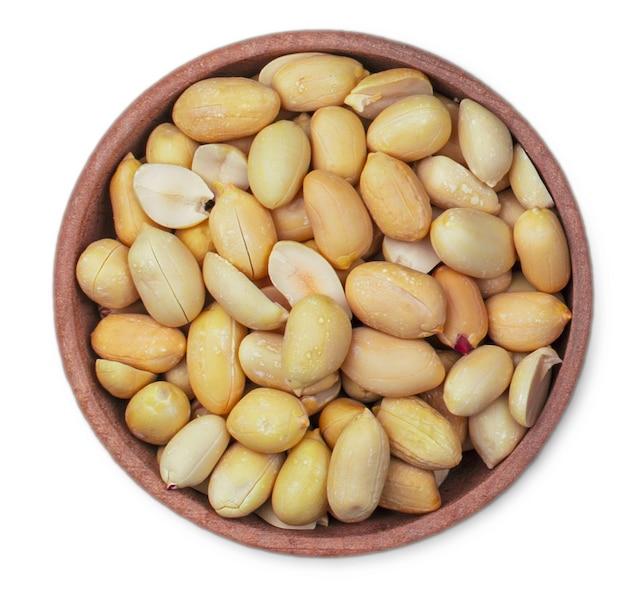 Le arachidi tostate in una tazza bianca isolata su sfondo bianco