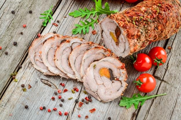 Rotolo di maiale arrosto farcito con albicocche secche, formaggio e noci, su un tavolo di legno