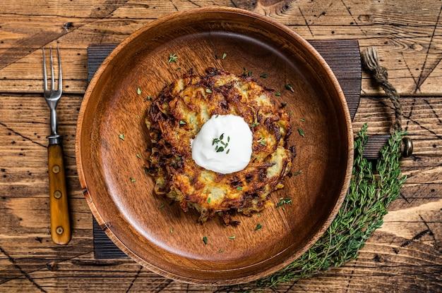 Frittelle di patate arrosto o frittelle alle erbe in un piatto di legno. tavolo di legno. vista dall'alto.