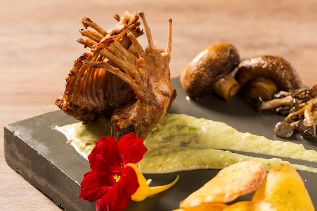 Quaglia arrosto con rosmarino e spezie sullo sfondo di legno.