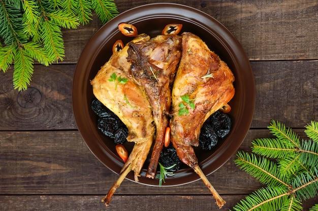 Coscia di coniglio arrosto con prugne su un piatto di ceramica su fondo di legno scuro