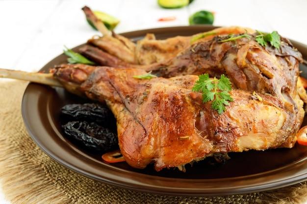 Coscia di coniglio arrosto con prugne su un piatto di ceramica su sfondo chiaro