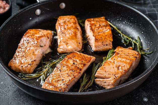 Bistecca di filetto di salmone arrosto in padella con rosmarino. sfondo nero. vista dall'alto.