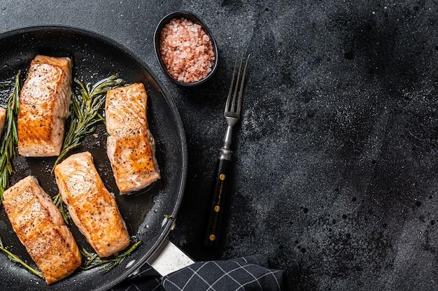 Bistecca di filetto di salmone arrosto in padella con rosmarino. sfondo nero.