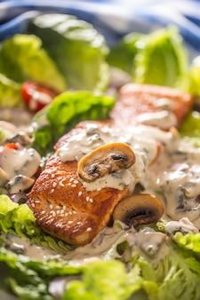 Filetto di salmone arrosto con insalata di verdure fresche pomodori funghi salsa e sesamo.