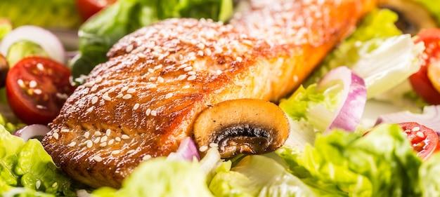 Filetto di salmone arrosto con insalata di verdure fresche pomodori funghi e sesamo.