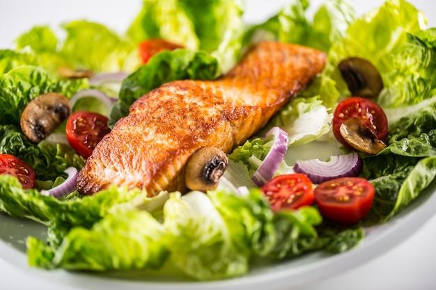 Filetto di salmone arrosto con insalata di verdure fresche su piatto bianco.