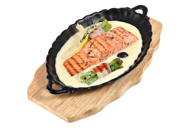 Salmone arrosto in salsa bianca e asparagi verdi grigliati isolati
