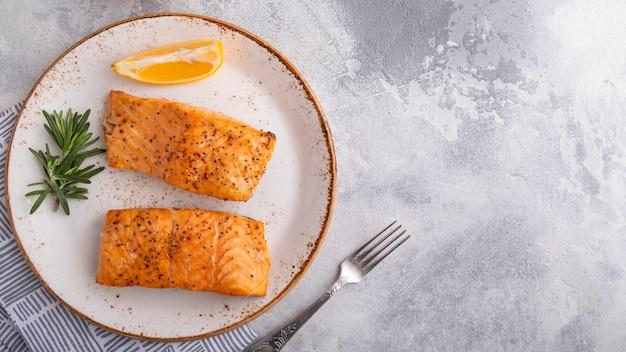 Salmone arrosto con spezie. delizioso pesce cotto con il limone su un piatto. vista dall'alto. copia spazio