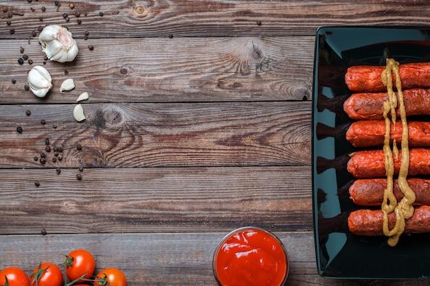 Salsiccia arrosto in banda nera sulla tavola di legno. vista dall'alto con spazio vuoto per testo, logo, ecc.