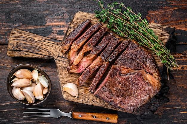 Bistecca di carne di manzo di manzo arrosto e affettato su un tagliere di legno con timo