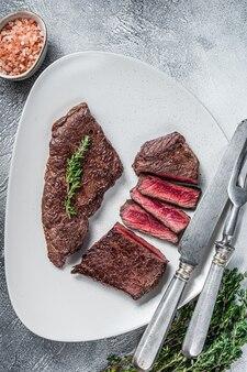 Arrosto di manzo affettato bistecca di carne di manzo su un piatto con timo. sfondo bianco. vista dall'alto.